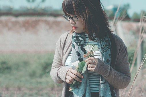白い花を手にした女性
