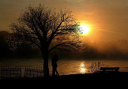 湖のほとりで抱きしめ合うカップル