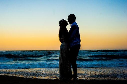 ビーチで抱き合う妊婦と男性