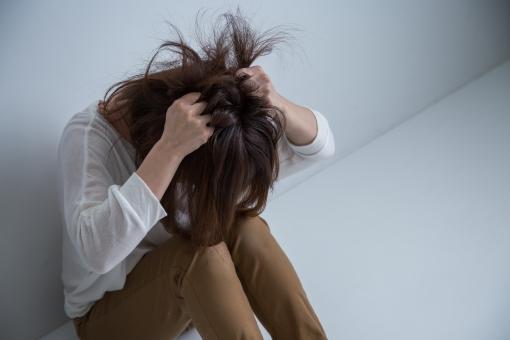苦悩して髪をかきむしる女性