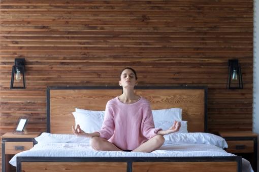 ベッドの上で座禅を組む女性