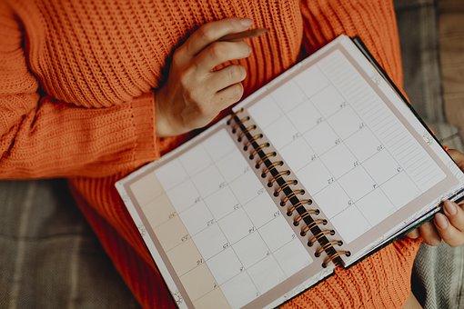 スケジュール帳に書き込む女性の手元