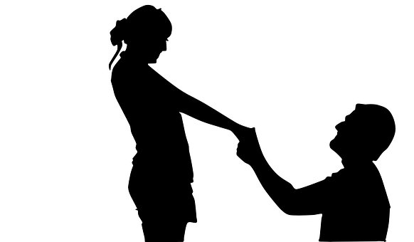 女性に跪く男性のシルエット