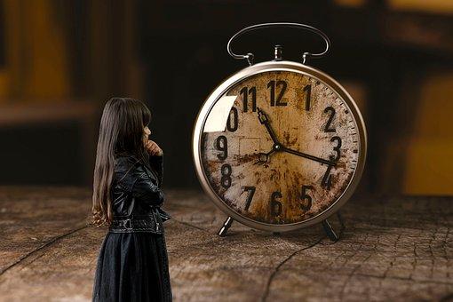古ぼけた時計を見つめる少女