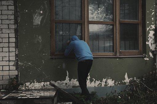 家の中をのぞき込む男性