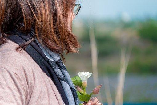 白い花を持った女性