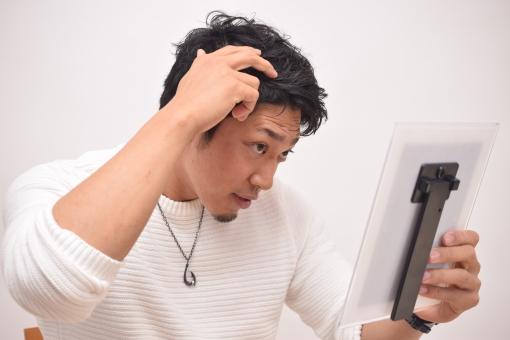 鏡で髪型をチェックする男性