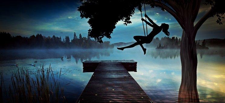 湖でブランコに乗る幻想的なシルエット