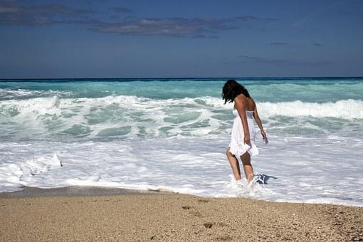 波打ち際にいる白いワンピース姿の女性