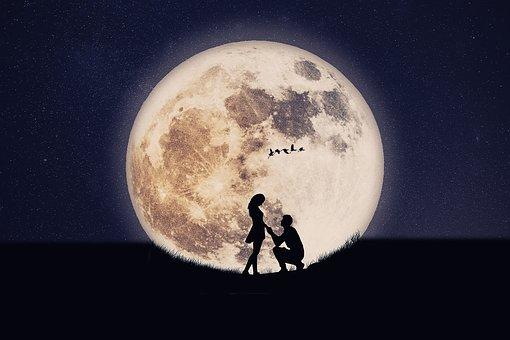 大きな月とプロポーズする男性のシルエット