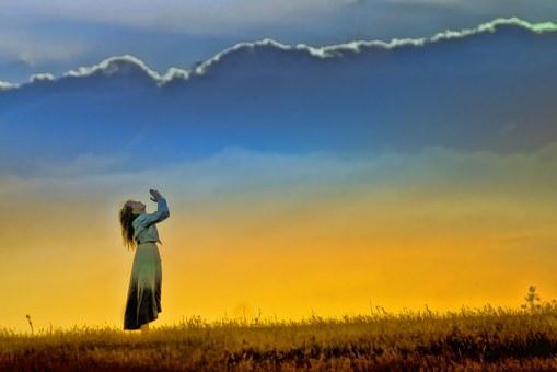 空に向かって祈る女性