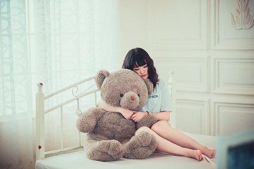 ベッドで熊の人形を抱きしめる女の子