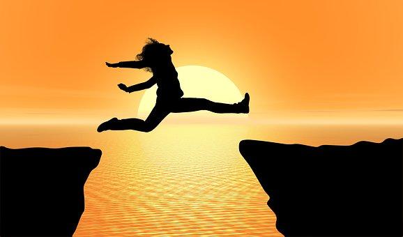 谷を飛び越える女性のシルエット