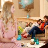 ソファーにいるカップルを見つめる女性
