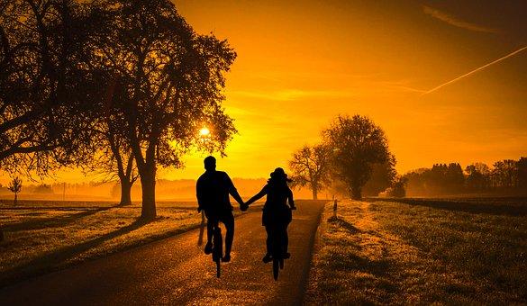 日没の田舎道を自転車で走るカップル