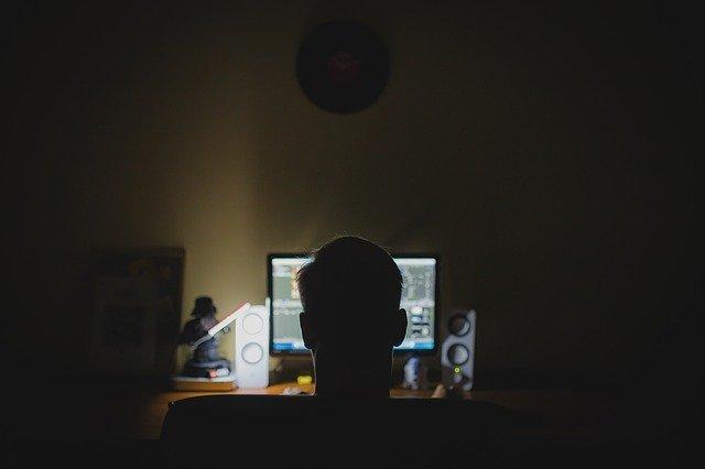 暗い部屋でPCを操作する男性の後ろ姿