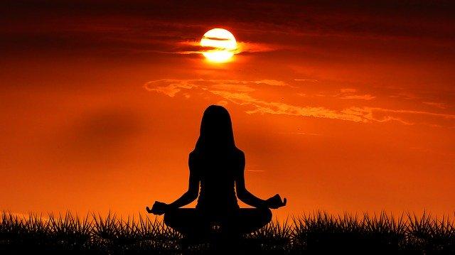 座禅を組んで瞑想する女性のシルエット