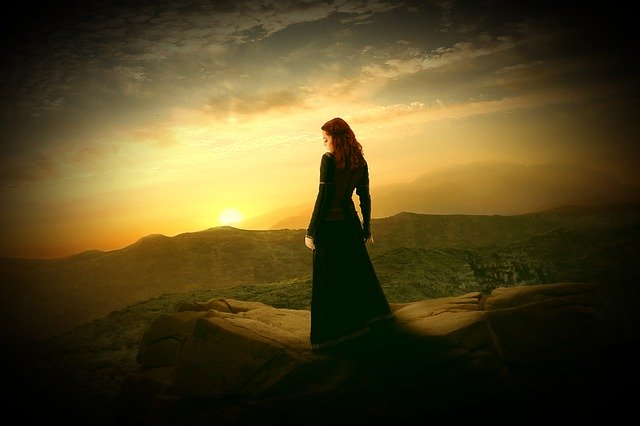 崖の先に立つ黒い服の女性